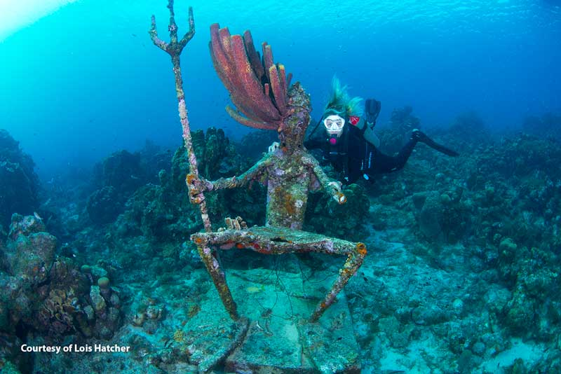 Female diver poses with statue of King Neptune